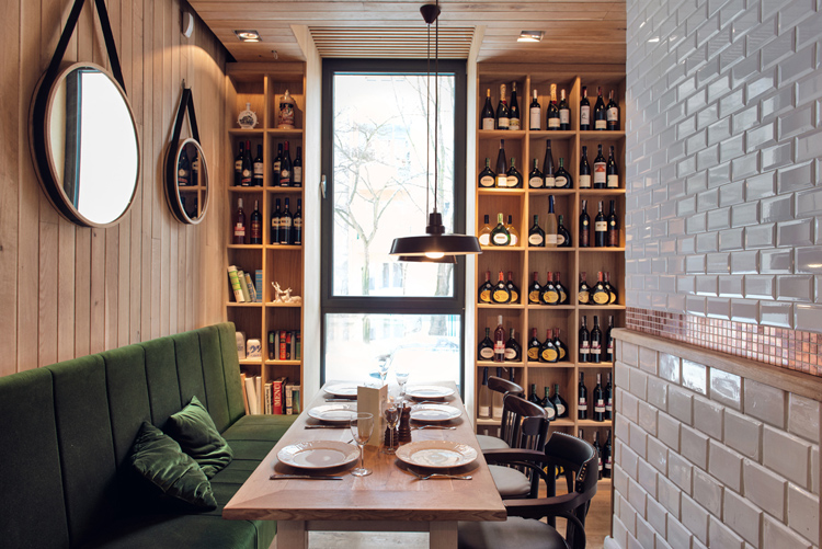 Althaus Restaurant, dining room, green velvet upholstery, white wall tiles, wine rack, timber wall panelling