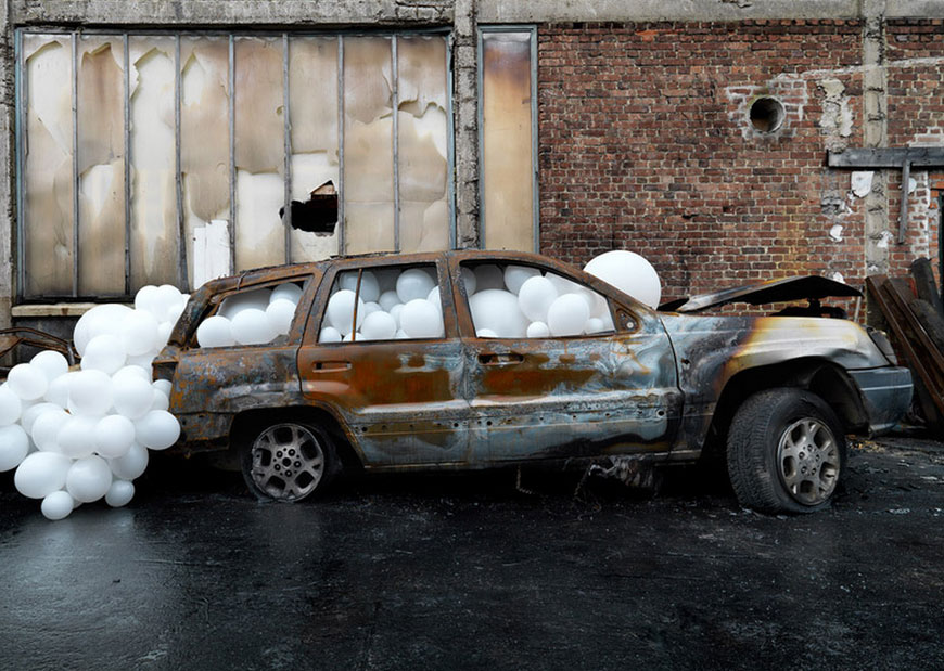 White balloons spill out the windows and doors of a house, invade a golf course and overflow from a burnt-out car in a series of installations by French artist Charles Petillon